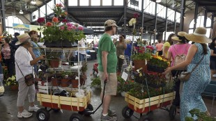 In this May 17, 2015 photo, Karl Bastian, of Traverse City, center, pulls a wagon full of plants with his daughter, Sophie Bastian, right, and his mother-in-law Theresa Perez, of Warren, Mich., left, during Flower Day at Eastern Market in Detroit. The Conference Board on Tuesday, May 26, 2015 said consumer confidence rebounded this month as the job market showed signs of improvement. (Robin Buckson/Detroit News via AP) DETROIT FREE PRESS OUT; HUFFINGTON POST OUT