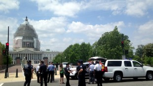Capitol Hill police and visitors stand outside the Capitol Visitors Center and the Capitol in Washington, Tuesday, May 26, 2015, after they were evacuated, closing area streets as alarms sounded in both buildings. A spokeswoman for U.S. Capitol Police said officers were investigating the cause of an audible alarm and had told people to leave the Capitol and the connecting visitors' center. Lawmakers were in recess this week for the weeklong Memorial Day break. (AP Photo/Alan Fram)