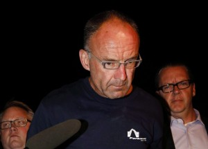 Douglas Garland is escorted into a police station in Calgary, Alta., Monday, July 14, 2014. Garland, accused of killing a boy and his grandparents nearly one year ago, has been ordered to stand trial. THE CANADIAN PRESS/Jeff McIntosh