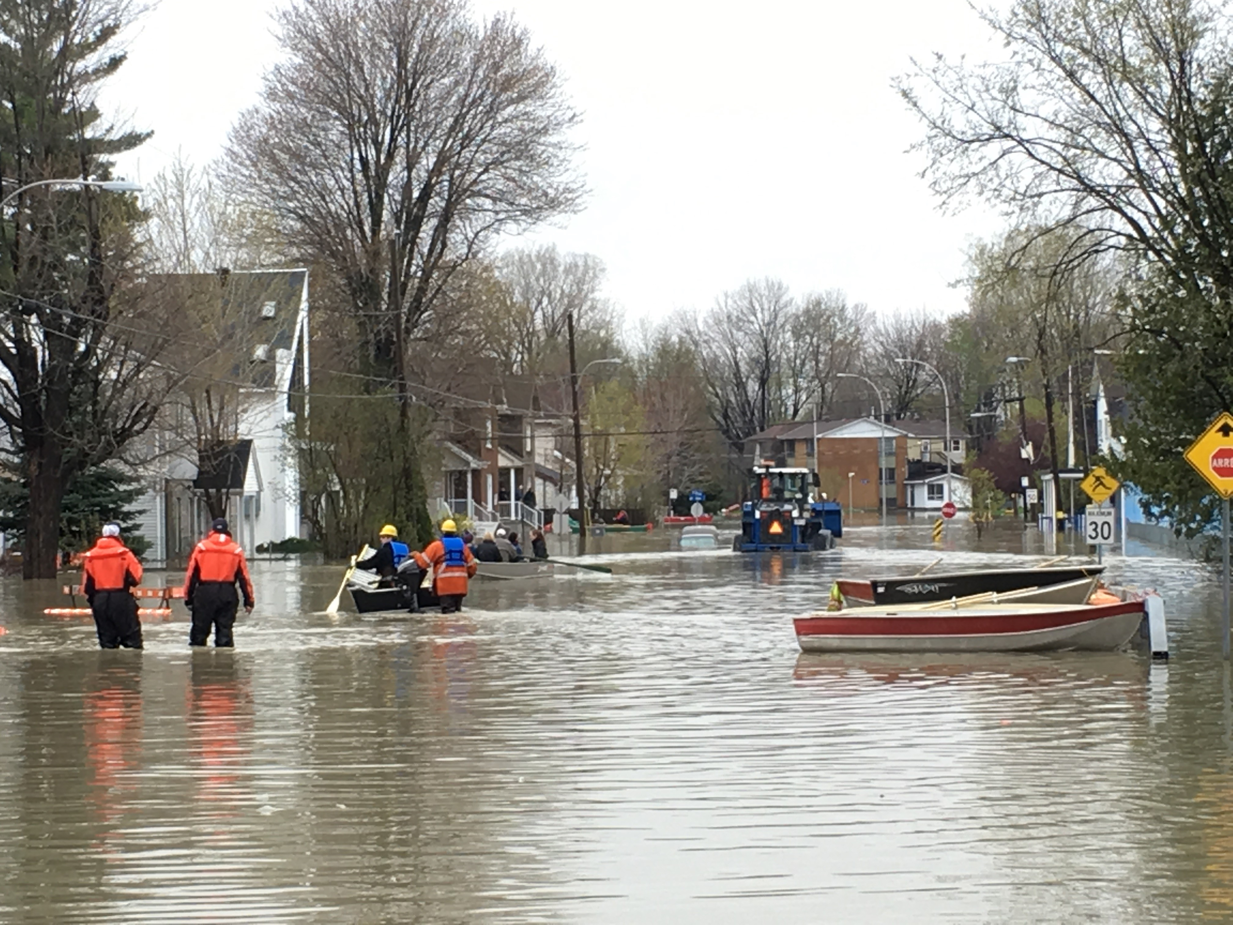 Boats and front loaders are used to rescue people from ...