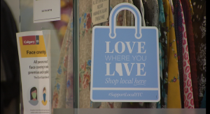 A decal in a store window encouraging shoppers to buy local.