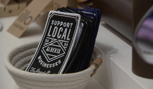 """A stack of patches at Collab in Southcentre Mall that read 'Support Local Alberta businesses""""."""